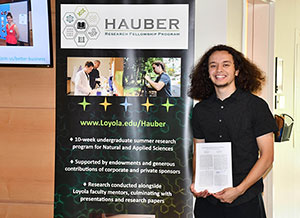 Chet Pajardo II posing next to the Hauber Fellowship sign with his paper