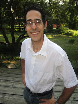 Photo of professor nicolino applauso against a park background. He has dark hair, glasses, and he is wearing a white button down shirt with short sleeves.