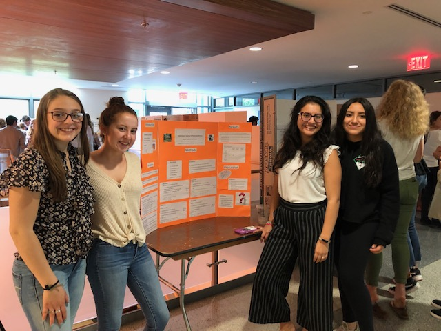 four undergraduate students posing with their poster presentation.