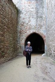 Dr. Barbara Vann posing in frint of a castle in the Czech Republic.