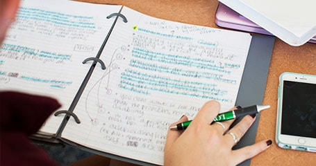 A student writing in their notebook
