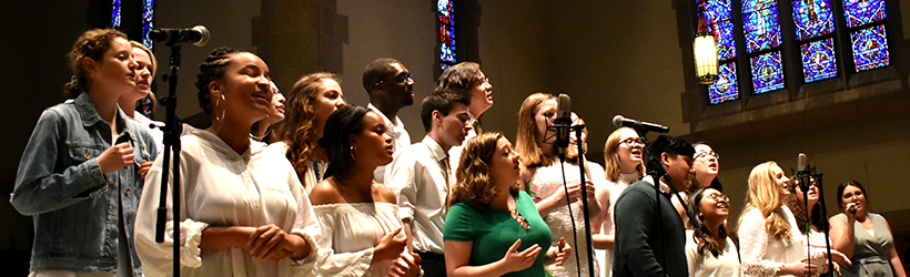 Students singing at front of chapel