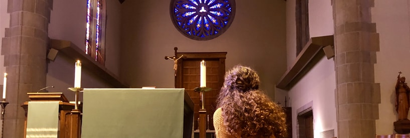 A student praying/reflecting at the alter of a chapel.