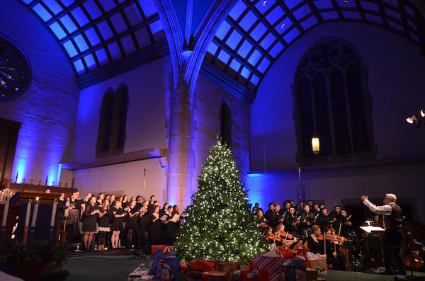 Chapel with blue lighting and Christmas tree with Chapel Choir in the background singing