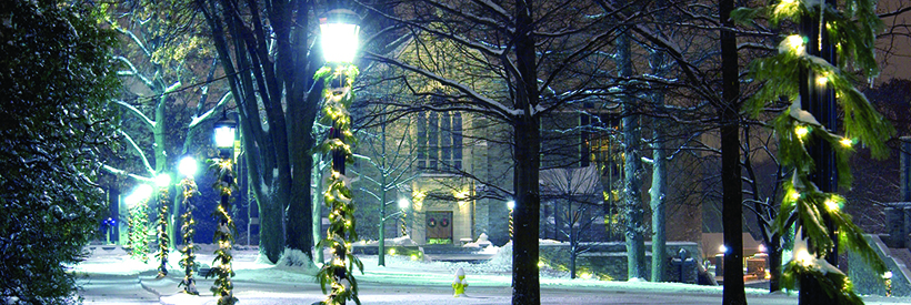 Holiday decor and snow on the Quad with Chapel in the background