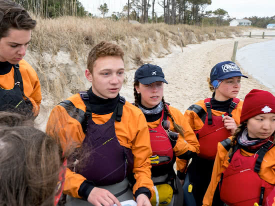 Students reviewing a map along the shore