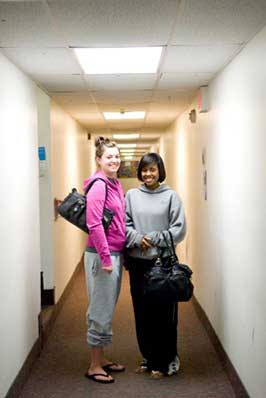 Two young women smiling in a hallway in Campion Tower