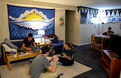 Students gathered in the living room of a Campion Tower residence