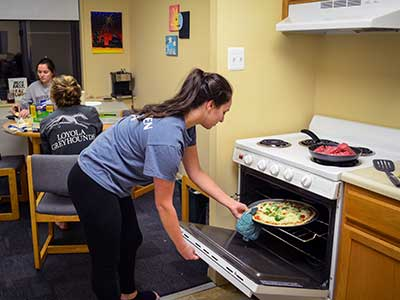 Student putting a pizza in oven at Campion residence as friends wait in the dining room