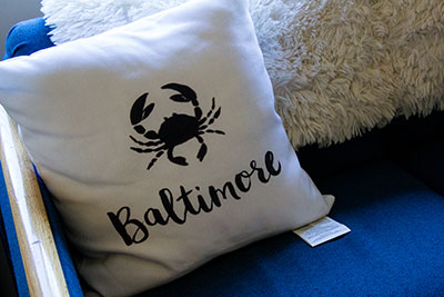 Pillow on dorm bed with crab reading 'Maryland'