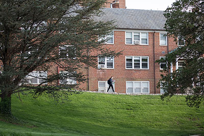 Student walking past a residence hall on the west side of campus between two trees