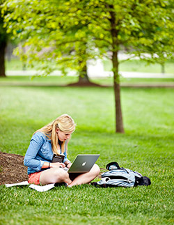 Student studying on grass