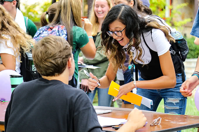 Student smiling at Activities Fair signing a form