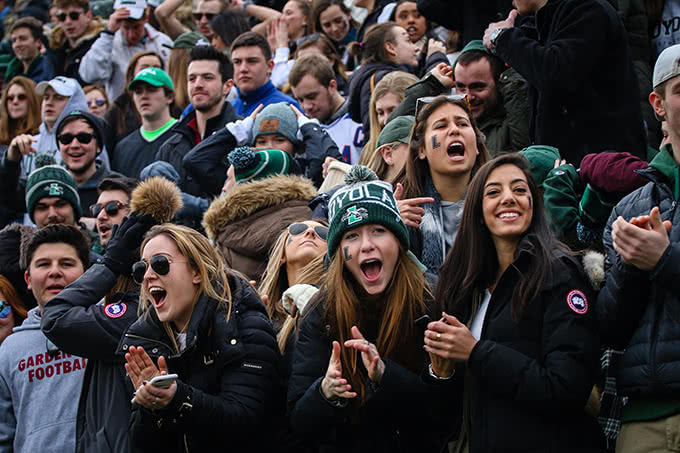 Students cheering with mouths open at lacrosse game