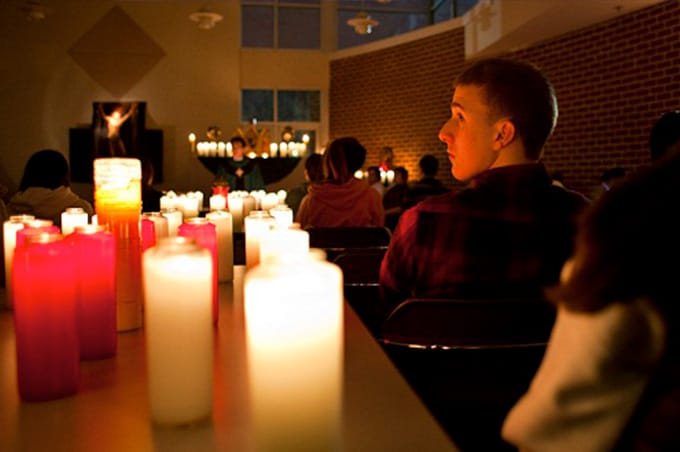 Student looking at candles in darkened room with altar at front