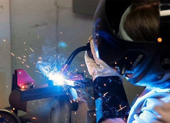 A student welding, with bright sparks flying everywhere
