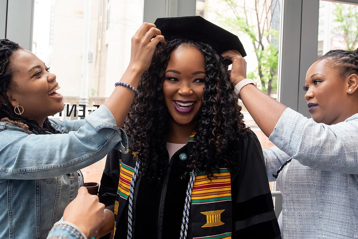 A graduating student smiles as two people pin a commencement hat on her head