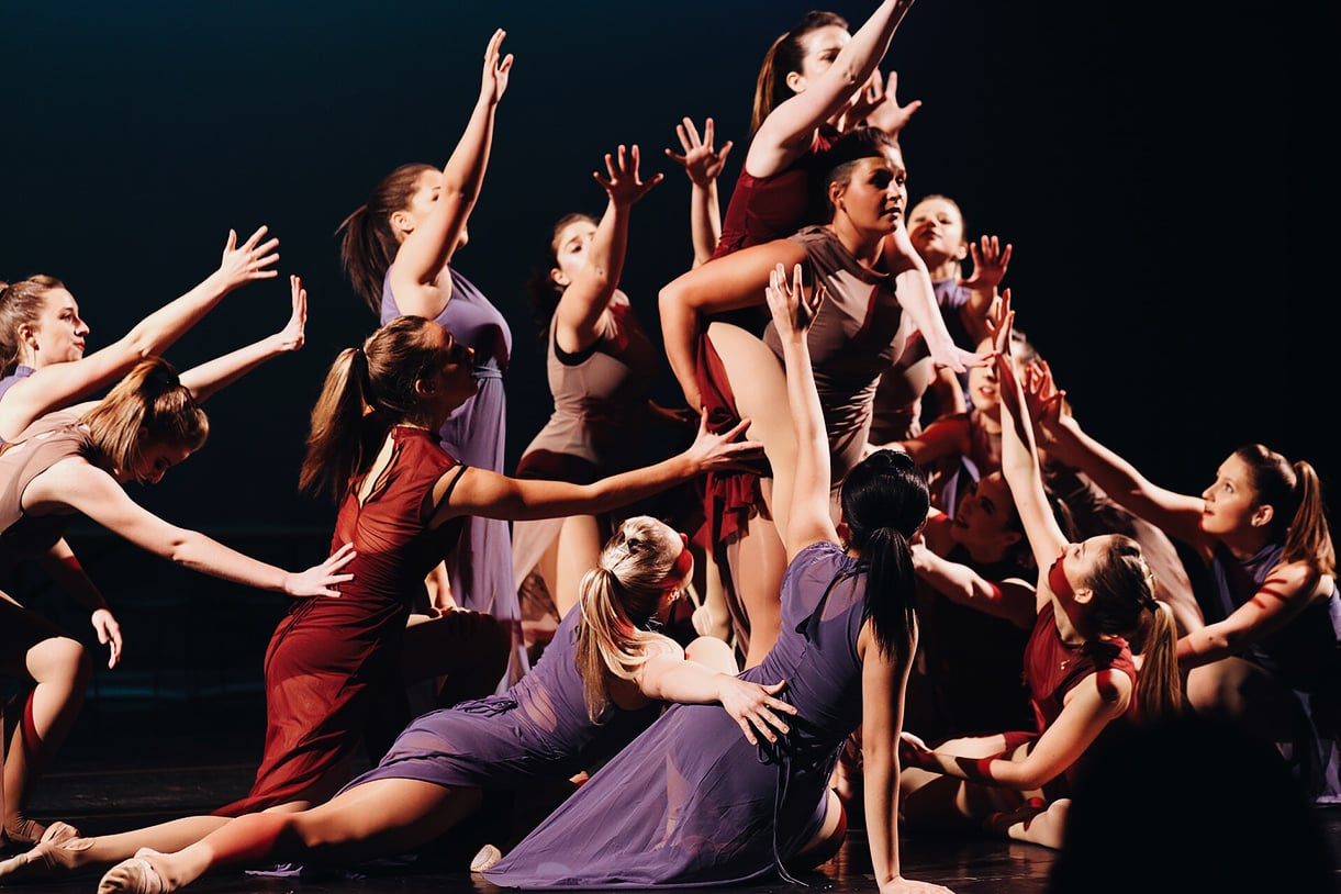 Loyola dancers posing together in a large group, wearing red, purple, and brown dresses in front of a black background