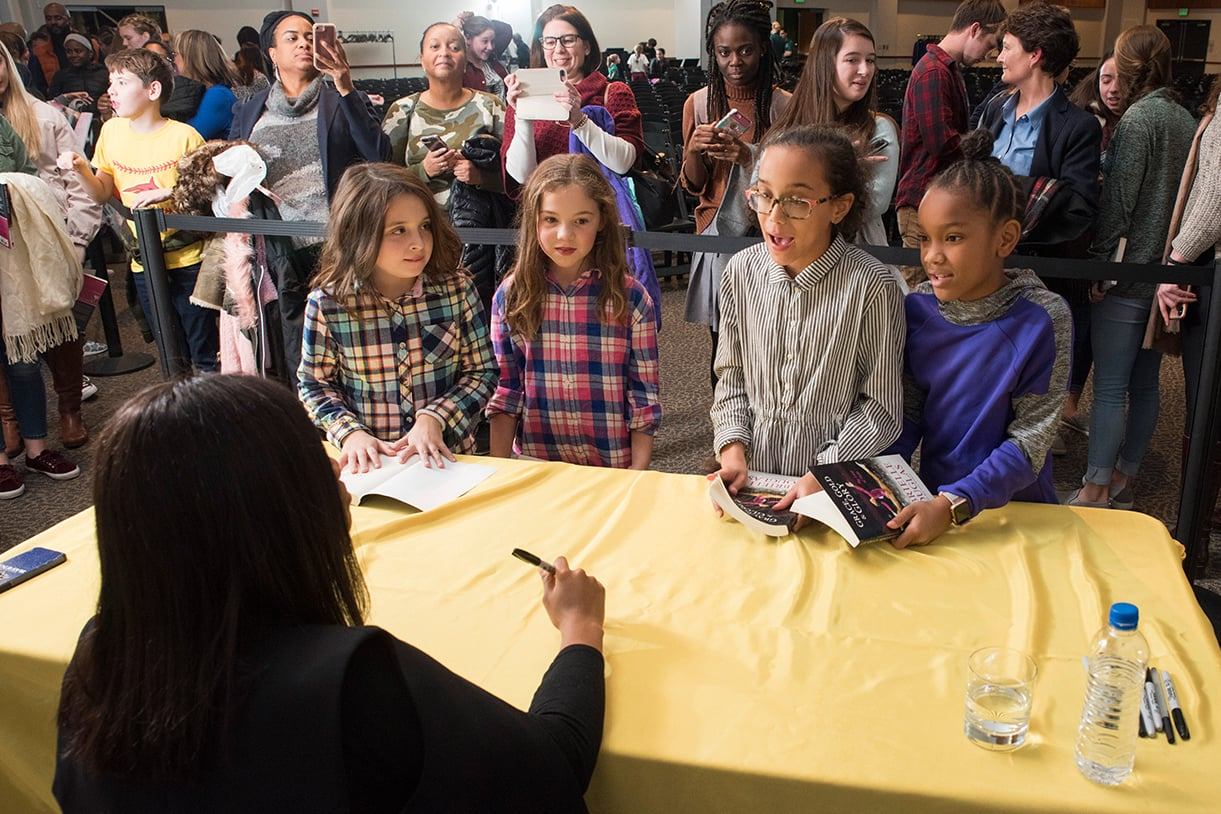 Young girls line up to have their books signed by Gabby Douglas