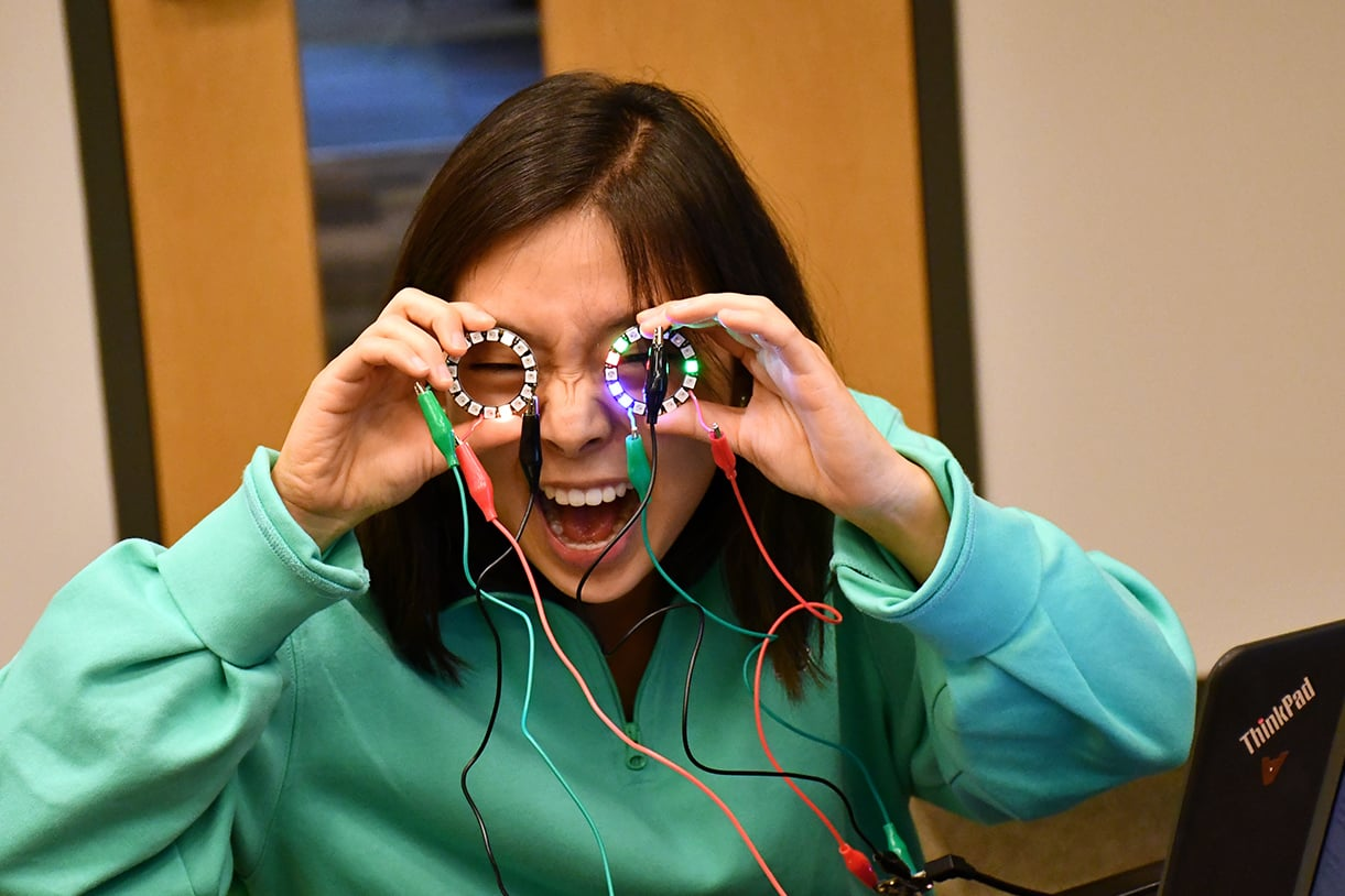 A student putting round electronic devices over her eyes like glasses and smiling