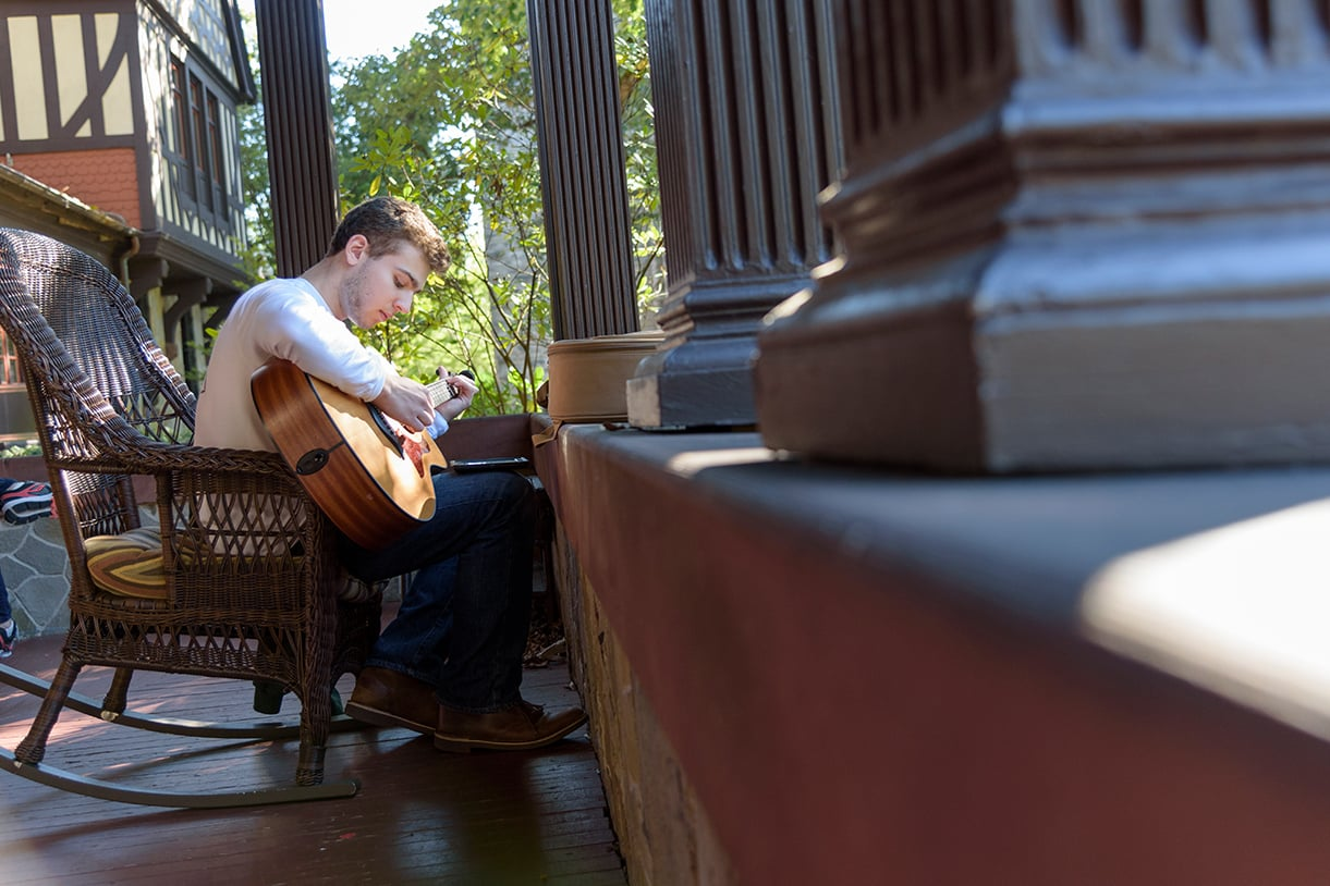 A student playing a guitar while sitting on a rocking chair on the Humanities building porch