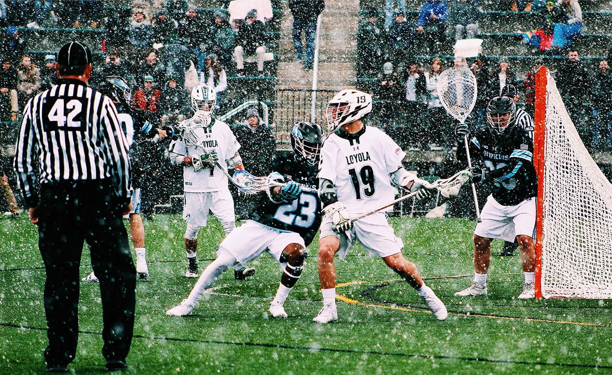 Loyola lacrosse players playing against Hopkins during a snowstorm