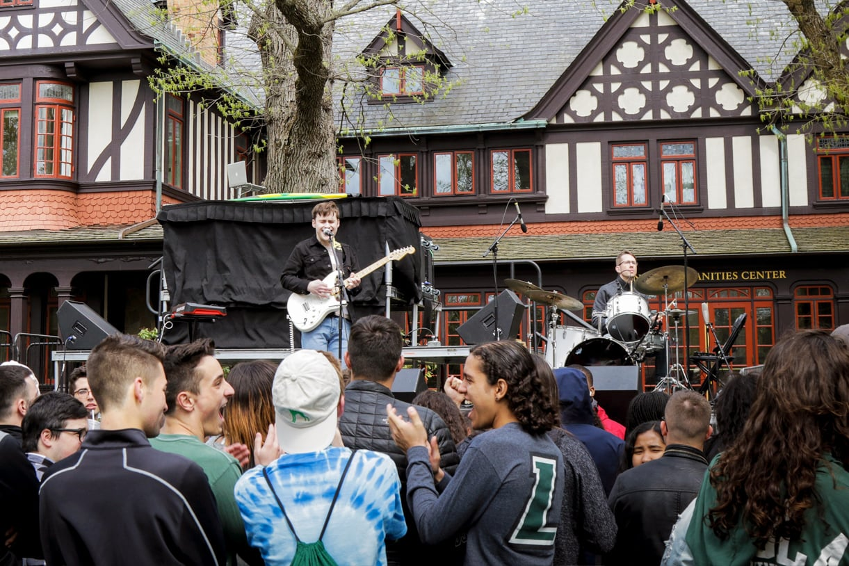 A band performs in front of the Loyola Humanities building, with a crowd cheering in the foreground