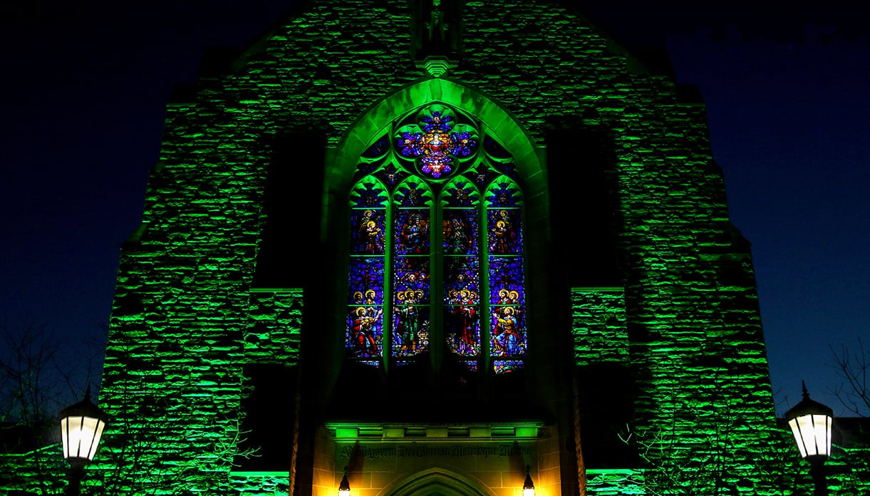The front of the Alumni Memorial Chapel lit up by green lighting at night