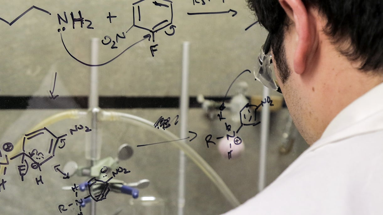 A chemist looking at a glass window with chemistry notes written on it in dry erase marker