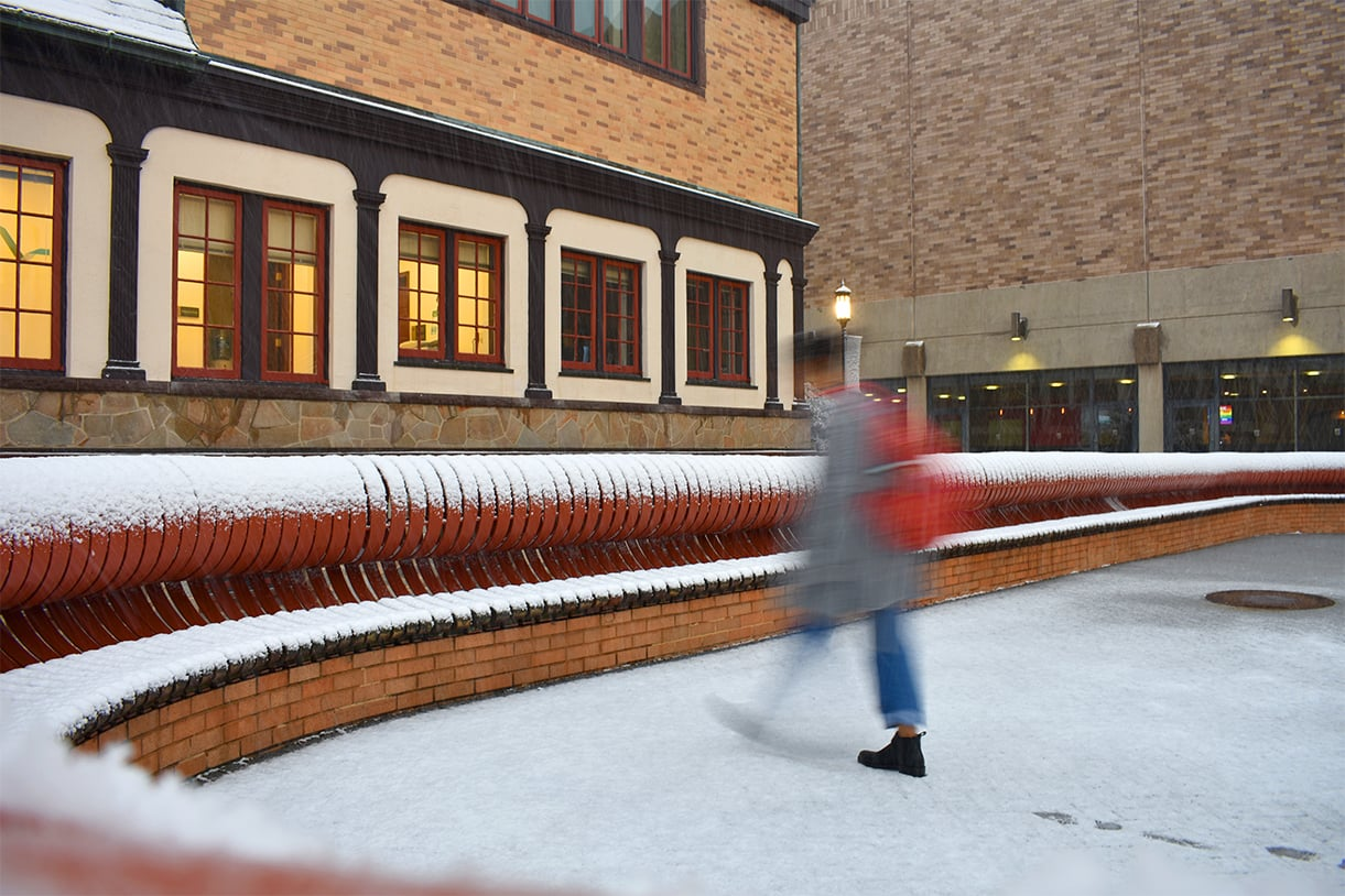 A blurred student is seen walking through the snow behind the Humanities building