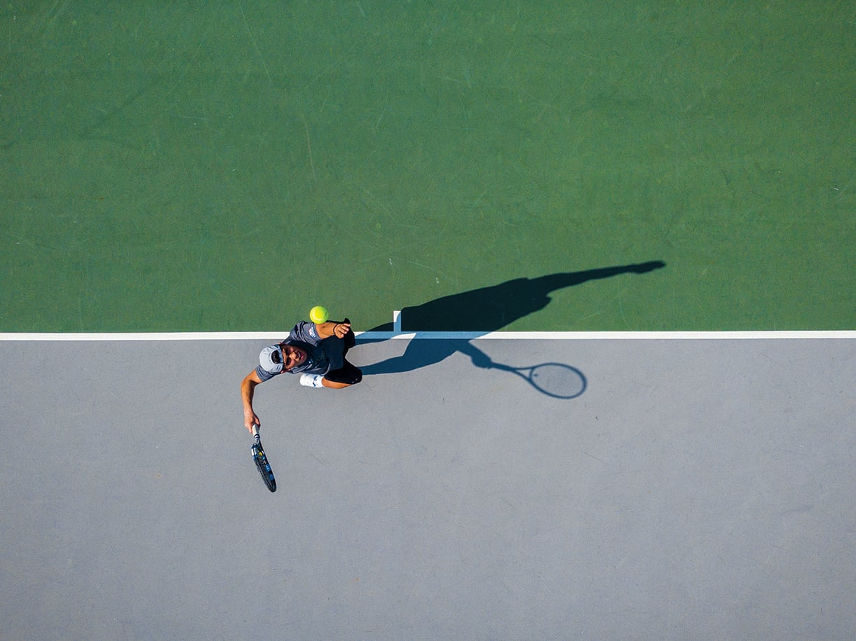 A birds-eye view of a player serving on a tennis court