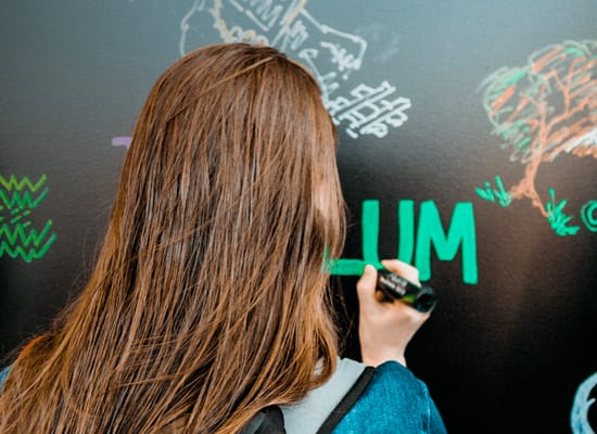 A student writing 'LUM' on a chalkboard, while other doodles can be seen on the chalkboard