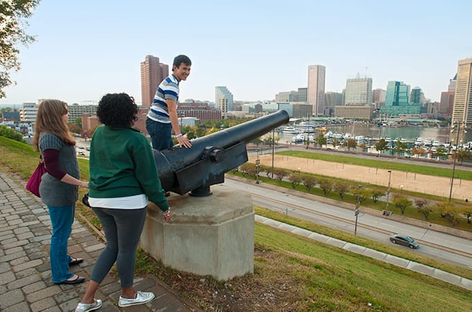 Students near an old cannon, looking toward Chesapeake Bay and downtown Baltimore