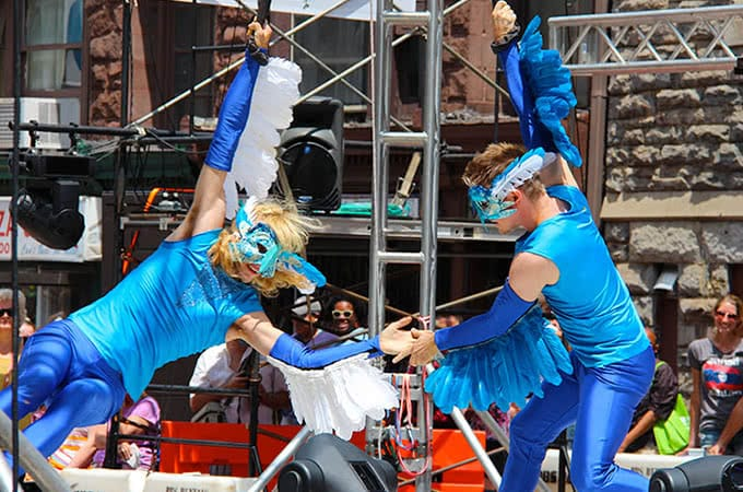 Entertainers wearing blue bird costumes and swinging on ropes