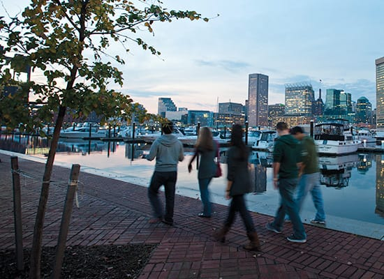 Students walking along the harbor at night with the Baltimore skyline in the background