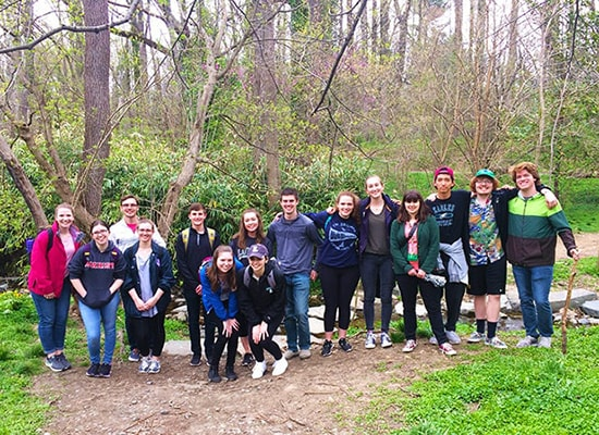 Honors students posing for a group photo on a wooded trail during a hike