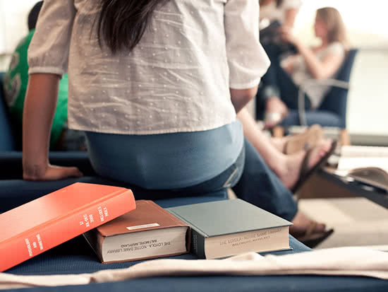 A student sits facing other students, with textbooks in the foreground