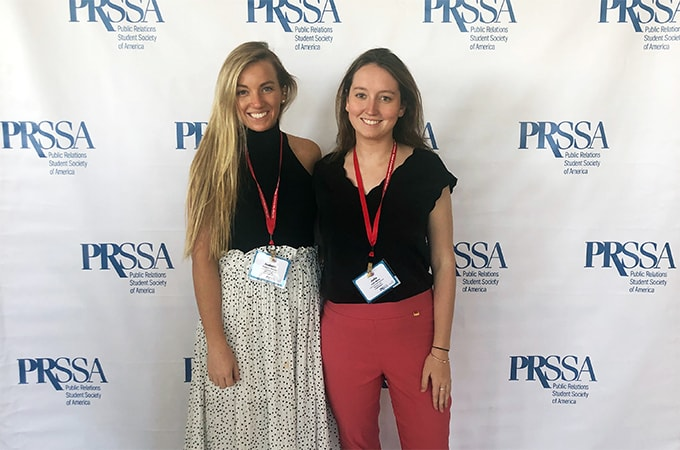 Isabelle Garrity and Julia Mulry posing for a photograph in front of a PRSSA step and repeat banner