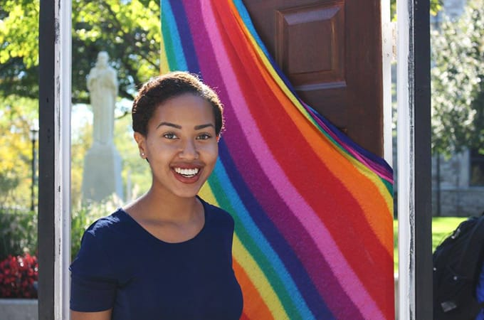 A female student standing outside in a doorframe with a rainbow flag draped on the door