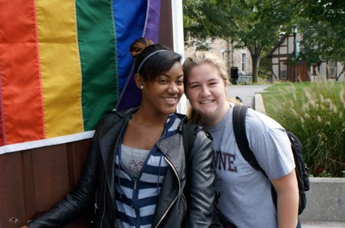 Two female students standing outside in a doorframe with a rainbow flag draped on the door