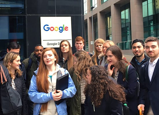 Students posing for a photo in front of a Google building