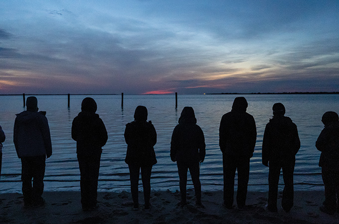Students look out to sea after the sunset.