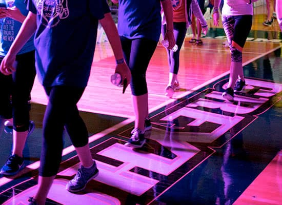 Closeup of students legs walking on a basketball court with purple lighting