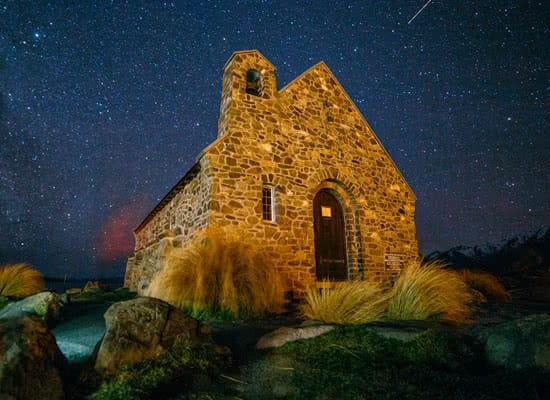 An old, small, stone building sits under the starry, night sky