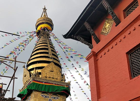 A large stupa with prayer flags next to a red building
