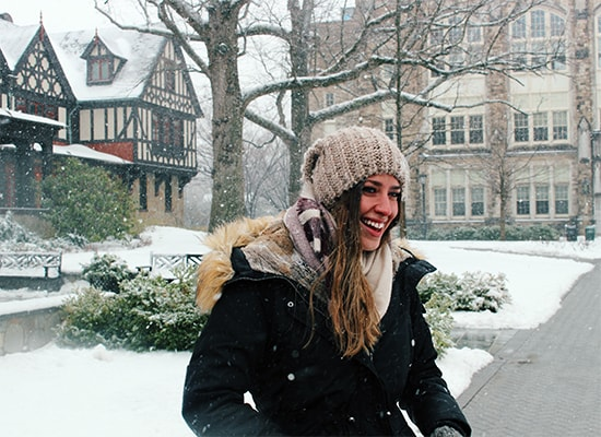 Abigail Vitaliano standing in front of the Humanities Building on a snowy day