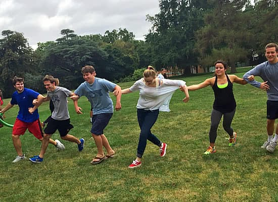 Several students running with arms linked in a grassy field