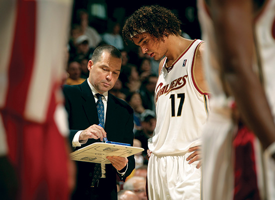 Malone speaks to a Cavalier player with his play board in hand, likely pointing to a game plan.