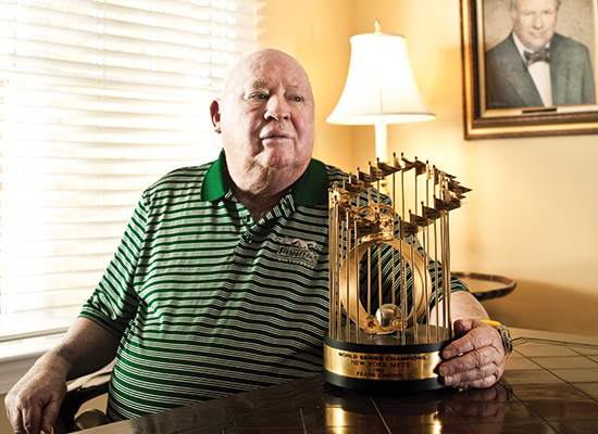 Frank Cashen sits in his home at table, with golden trophy.