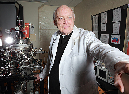 Fr. Haig next to astronomical device in physics lab.